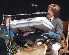 Colour photograph of Guillemots lead singer Fyfe Dangerfield performing live in 2006. He is sat behind a keyboard and singing into a microphone.