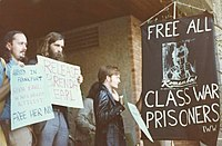 "People holding signs near a banner demanding, ""Free all class war prisoners!"""