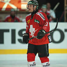 A Caucasian male ice hockey player shown from the knees up. He is wearing a red and white sweater with a dark helmet.