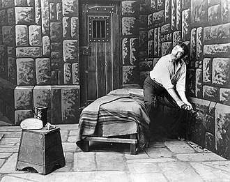 The Count of Monte Cristo - Edmond Dantès (James O'Neill) loosens a stone before making his escape from the Château d'If in The Count of Monte Cristo (1913)