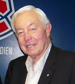Photo de Jean Béliveau devant le logo des Canadiens de Montréal