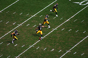 Four players run up the field as the kicker executes a kickoff