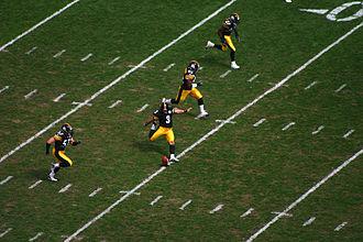 Четыре игрока выбегают на поле, когда выполняющий удар выполняет начальный удар