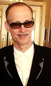 A balding man with a small mustache, wearing sunglasses and a dark suit.