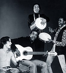 A black and white photo of a man with an acoustic guitar, surrounded by three other men holding percussion instruments