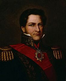 Half-length painted portrait of a man with curly hair, long sideburns and blue eyes who wears a heavily embroidered military tunic with high collar, gold braid epaulettes and a red sash of office