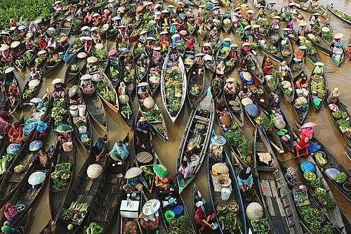 Торговля с лодок на плавучем рынке банджаров в Индонезии
