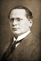 a picture of a young man with glasses wearing a suite and looking towards his left at the camera