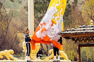 Flag of Bhutan - A large Bhutanese flag being lowered.