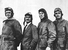 Four men, each wearing a flying helmet and goggles