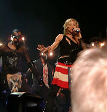 A blond woman on stage. She wears red-and-white striped skirt and is wearing a black top with zippers. She's singing into a microphone she holds with her arm. To her right there is a dancer wearing a mask and wearing black clothes. The head of a blonde audience member can be seen.