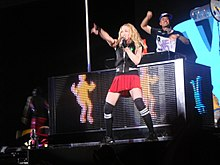 Madonna dancing on a DJ's desk wearing red shorts and a black sleeveless shirt. She's holding on to a pole with her left hand and holds a microphone to her mouth with her right hand.