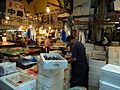 Man preparing fish beside fish stocks at the Tsukiji fish market, Tokyo, Japan.jpg