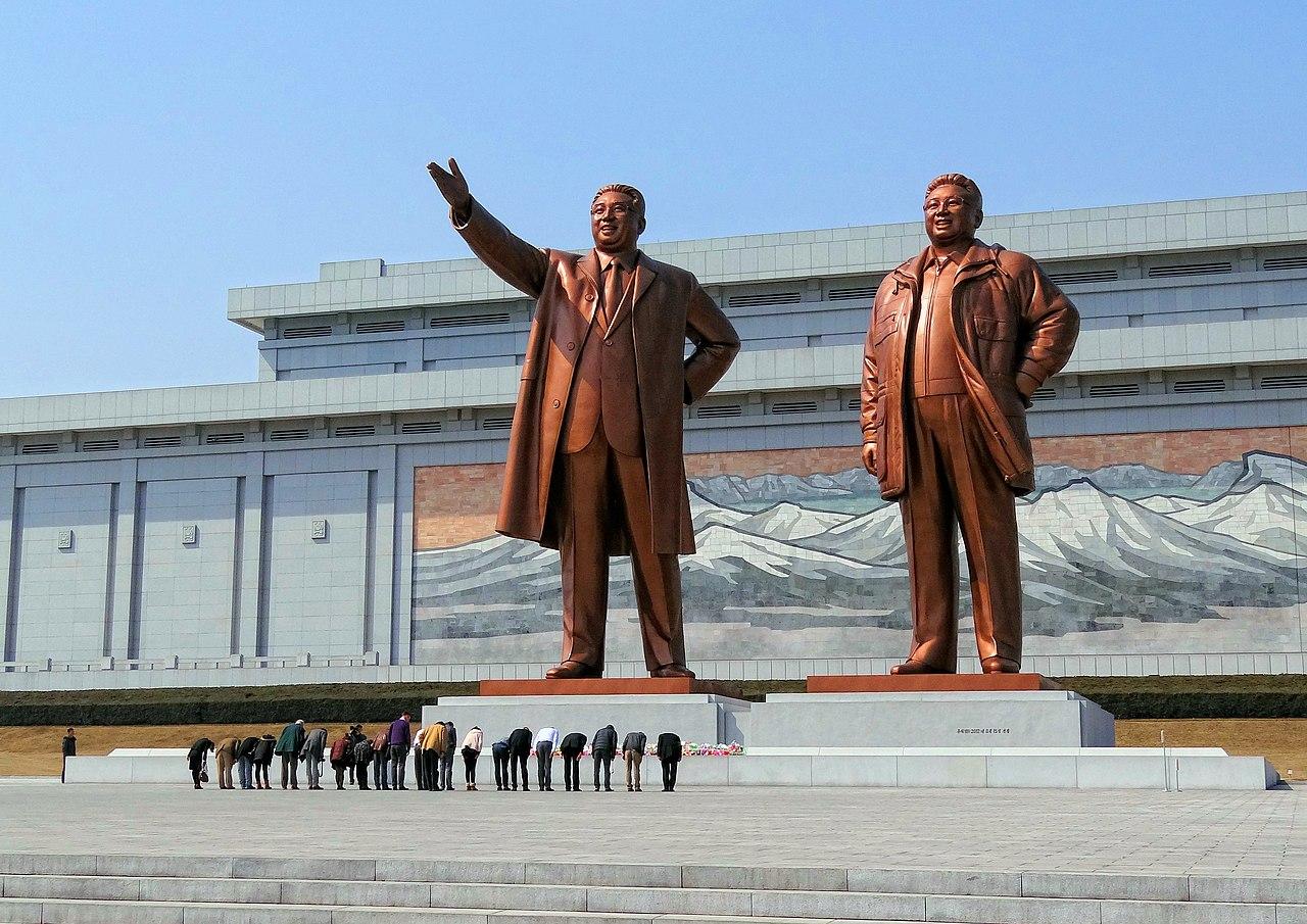Warga Korea Utara menghormati patung Kim Il-sung (kiri) dan Kim Jong-il di Monumen Besar Mansudae.