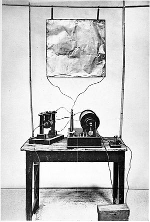 Guglielmo Marconi - Marconi's first transmitter incorporating a monopole antenna. It consisted of an elevated copper sheet (top) connected to a Righi spark gap (left) powered by an induction coil (center) with a telegraph key (right) to switch it on and off to spell out text messages in Morse code.