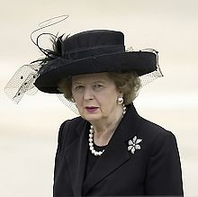 Thatcher in a black suit and hat, with a solid white background.