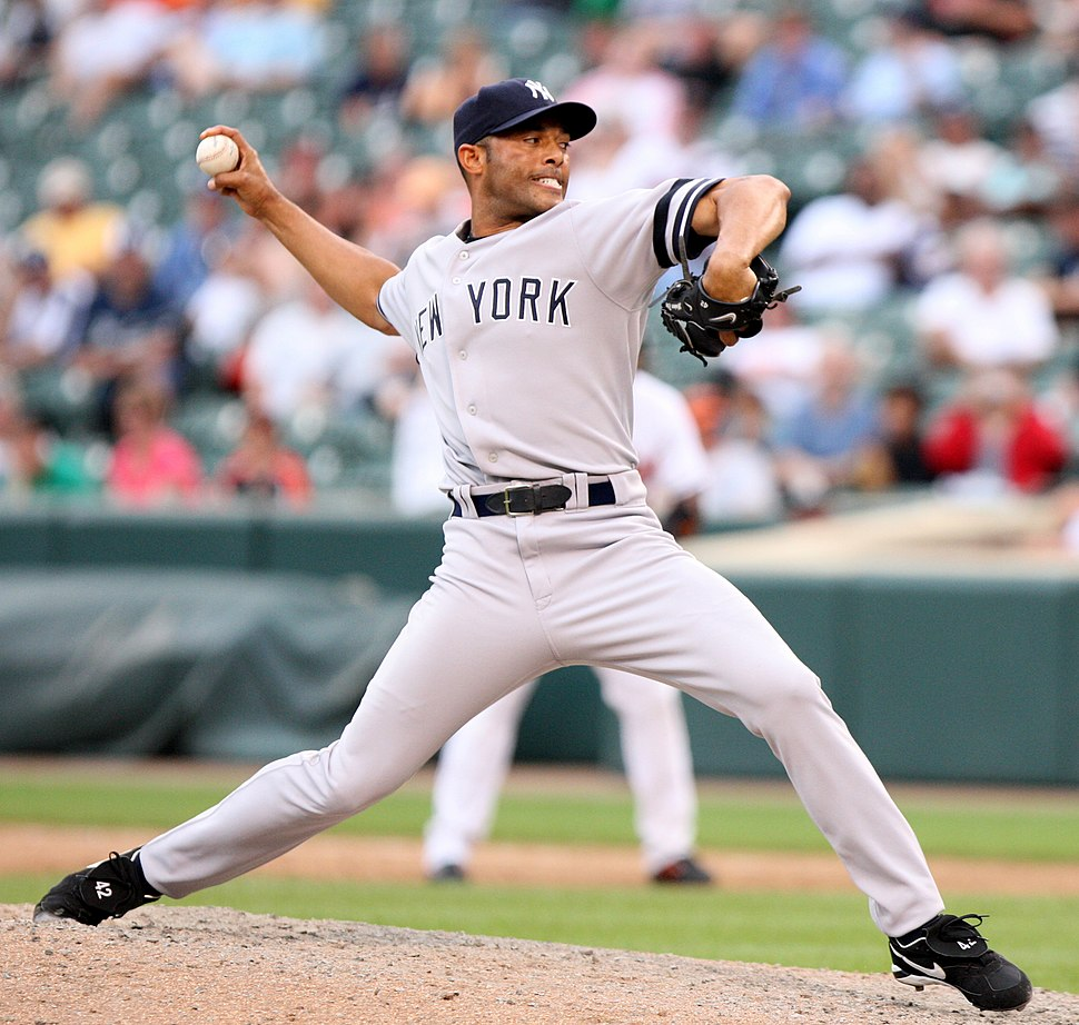 """Mariano Rivera in a gray baseball uniform and navy blue cap stands on a dirt mound. He is striding forward to the right as he clutches a baseball behind his head. His uniform reads """"New York"""" in navy blue letters across the chest. His face is contorted in concentration."""