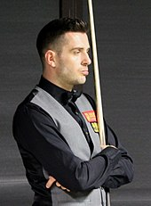Mark Selby standing with arms folded, snooker cue held in front of him, wearing black shirt & grey waistcoat