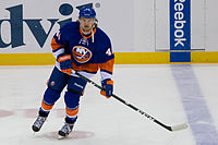 Michael Grabner skating on the ice with his hockey stick.