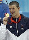 Michael Phelps holding up a gold medal