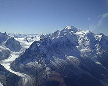 Snow-covered mountains and peaks of Mont Blanc with a long glacier flowing down towards the valley
