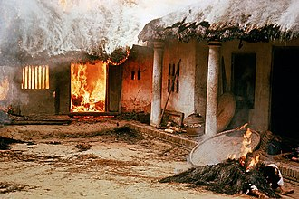 My Lai Massacre - Dead bodies outside a burning dwelling