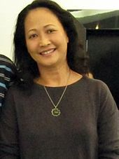 Nhu Quynh in 2010, looking forward and smiling, wearing a grey shirt and a necklace