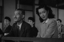 A theatre at which a Noh play is being performed: Prof. Somiya is wearing a business suit and tie and Noriko is wearing a simple, Western-style dress with a collar; Shukichi is looking straight ahead towards the left frame of the picture, smiling, and Noriko, not smiling, is looking toward the right frame of the picture towards an unseen person.