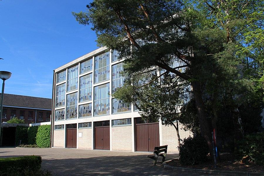 """De kerk O.L.V. van Altijddurende Bijstand werd  gebouwd tussen de jaren 1962-1968 en op 5 september 1968 ingewijd. De architect was René van Steenbergen (1911-1995). Hij tekende voor Den Hout een kerk met een sobere vormgeving waarvan het religieuze karakter niet """"aan uitwendigheden vastzit"""". Het kerkgebouw bestaat in feite uit drie strakke balkvolumes: het kerkschip, de lagere weekkapel met de sacristie en de rijzige klokkentoren. Hoe simpel van vormgeving ook, toch straalt de voorgevel een sterke aantrekkingskracht uit. Daarvoor zorgt een imposant, in regelmatige vakken verdeeld vlak van gekleurd glaswerk,   uitgevoerd door glazenier Joz. Beeck uit Mechelen."""