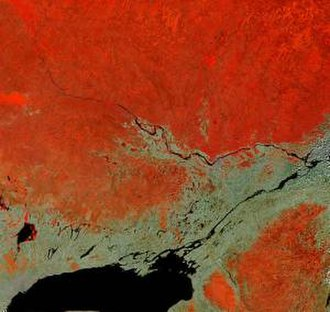 Ottawa River - In this false-colour satellite image, the Ottawa River flows southeast, joining the St. Lawrence River which flows northeast. Heavily forested areas appear differing shades of orange/red, while farmland is tan shades.