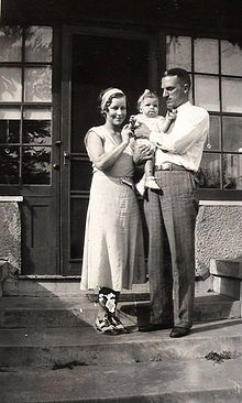 A couple stand on the front steps of a house. The man, aged about 30, dressed in grey flannels and a white shirt, holds a baby girl in his arms and gazes at her, the woman, dressed in a frock and co-respondent shoes from the 1930s stands next to them, touching the baby girl and smiling at the camera. The baby is dressed in a white frilly frock, white shoes and with a white ribbon in her hair.