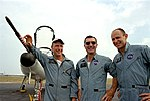 Pete Conrad (left), Dick Gordon, and Al Bean pose next to a T-38.jpg