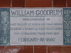 "A tablet formed of six standard sized tiles, bordered by green flowers in the style of the Arts and Crafts movement. The tablet reads ""William Goodrum signalman aged 60 lost his life at Kingsland road bridge in saving a workman from death under the approaching train from Kew February 28, 1880""."