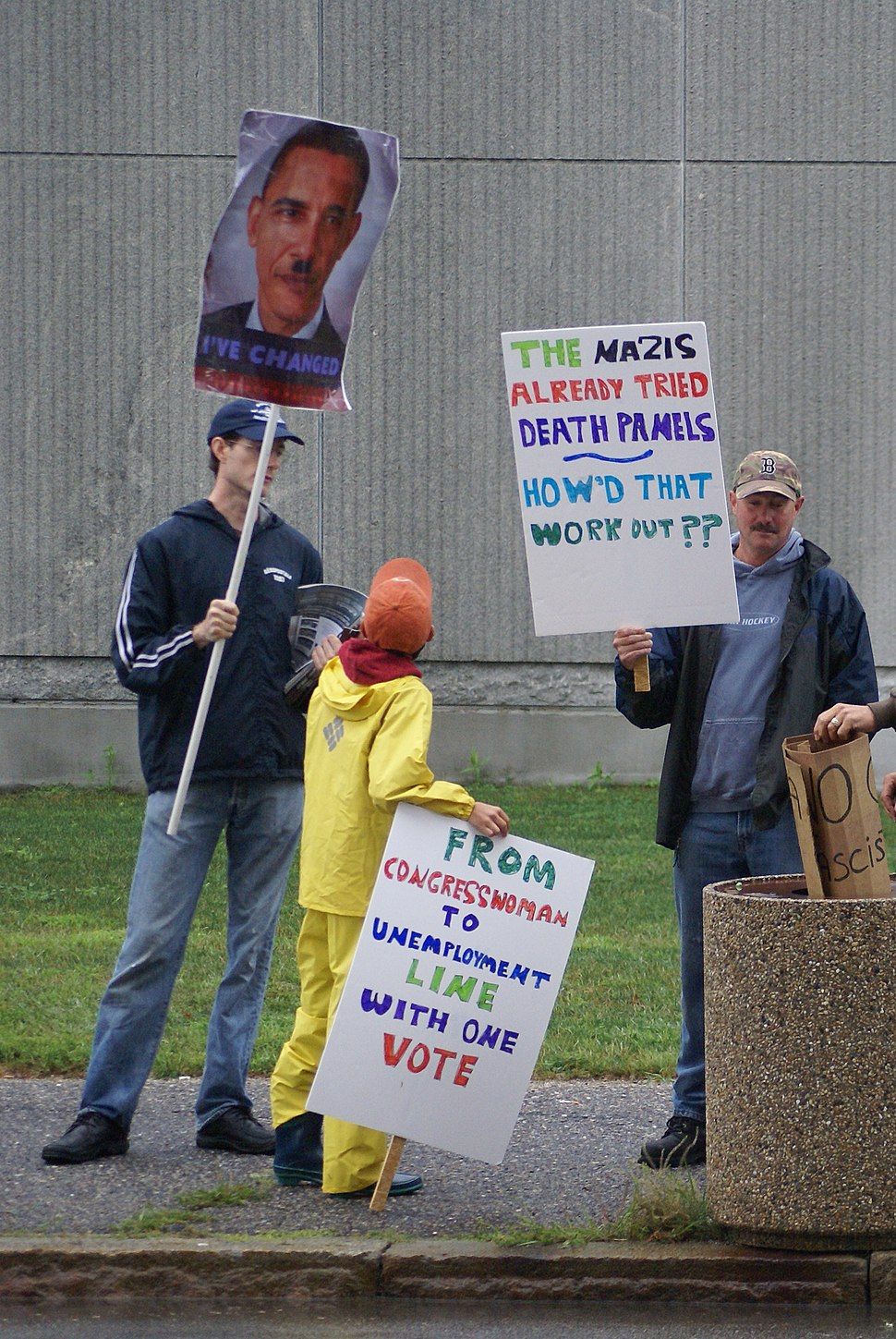Protest banners with picture of Obama with Hitler mustache and a death panel sign