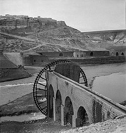 Al-Rastan (on hill in background) and waterwheel (forefront) separated by Orontes River, 1930s