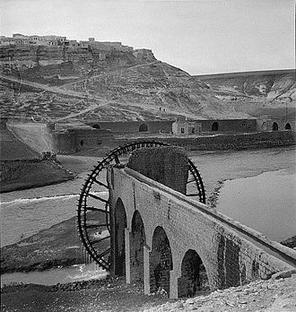 Al-Rastan - Ar-Rastan (on hill in background) and waterwheel (forefront) separated by Orontes River, 1930s