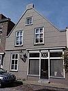 foto van Huis met witgepleisterde tuitgevel en schuiframen