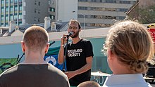 Sri speaking to a crowd outside Queens Wharf, Brisbane