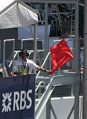 A man in a white overall, standing behind a blue placard with the letters RBS in white. He is waving a red flag.