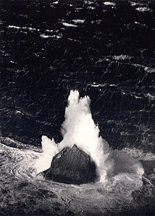 A back and white aerial image of an isolated and steep-sided rock in the midst of a stormy sea. A large wave has broken on the rock and sent fountains of white water high into the air.