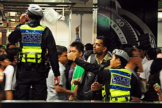 Public Transport Security Command - TransCom officers surveying and directing the public on New Year's Day in 2010 at City Hall MRT Station. Note the grey beret that was just introduced two days before on 30 December 2009.