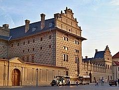 L'imposante façade à pignons et sgraffites d'un palais, de couleur grise mais éclairée par le soleil couchant, avec un train touristique en stationnement.