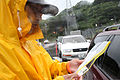 Security guard Atsushi Shimabukuro checks identification documents at the gate of U.S. Marine Corps Base Camp Smedley D. Butler in Okinawa, Japan, Oct. 28, 2010, as the area is hit by rain and wind from Typhoon 101028-M-VG363-037.jpg