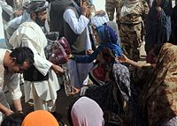 Shadi Khan, the Tarnak Wa Jaldak district governor, hands out humanitarian aid supplies to female students of the newly opened Shar-e Sara Girls School during a civil affairs humanitarian aid project in Zabul 110913-N-AT856-075.jpg