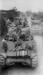 tanks with several men sitting on its turret advancing along road towards camera
