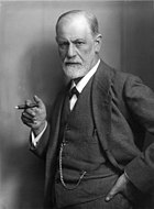 photograph of a balding man with a beard; holding a cigar and wearing a suit