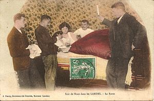Wedding customs by country - Wedding evening in the Landes: Three people bring la roste (roasted bread soaked in sweet wine) to a couple of newlyweds in bed. Map postally used on July 16, 1914.