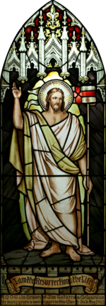 "High resolution, perspective corrected stained-glass image of Jesus with a halo, dressed in white and gold robes, with his hand raised, and the banner ""I am the Resurrection and the Life"", together with a dedication to a deceased parishioner"