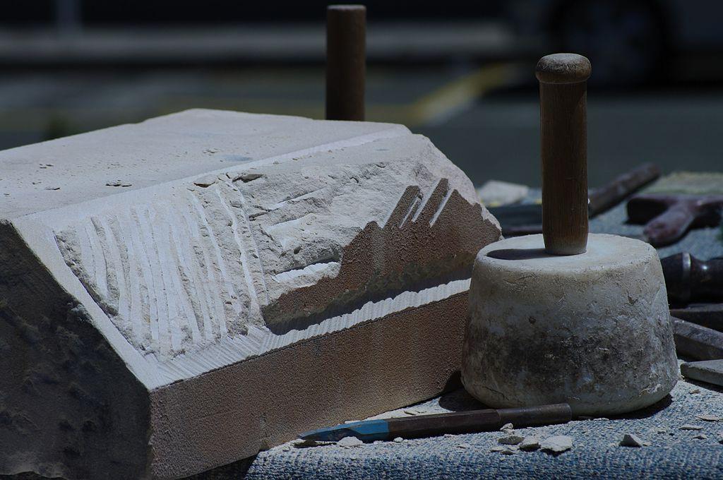 Stigmates de fabrication sur le marbre d'un chapiteau laissés par le maillet et la pointerolle présentant eux-mêmes des traces d'usure