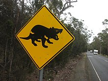 A square-shaped metal tilted at 45 degrees on a metal post. The sign is painted yellow with a picture of a black devil in profile. It is at the side of a straight road cutting through wooded forest and two vehicles can be seen.
